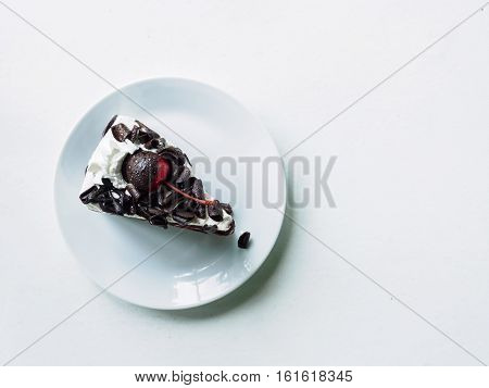 White cream cheery and chocolate of face cake slice on plate of white desk background Top view and copy space