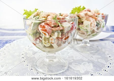 Salad with shrimp, avocado, tomato and mayonnaise, green salad in a glass goblet on a white napkin against a background of blue linen tablecloth