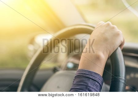 woman hands of a driver on steering wheel of a car with copyspace