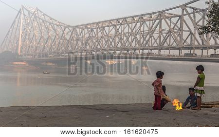 KOLKATA, INDIA - DECEMBER 11, 2016: Street children keep warm on a cold foggy winter morning at Mallick ghat near Howrah bridge at the bank of river Hooghly.