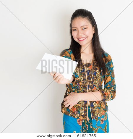 Portrait of young southeast Asian woman in traditional Malay batik kebaya dress hand holding a white blank paper card, standing on plain background.