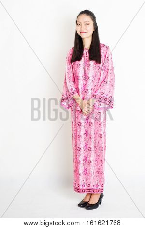 Portrait of young southeast Asian woman in traditional Malay batik dress smiling, standing on plain background.