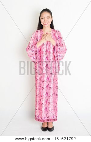 Portrait of young southeast Asian woman in traditional Malay batik dress greeting, standing on plain background.