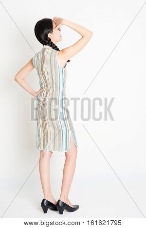 Rear view of young Asian woman in traditional qipao dress hand shielding, full length standing on plain background.