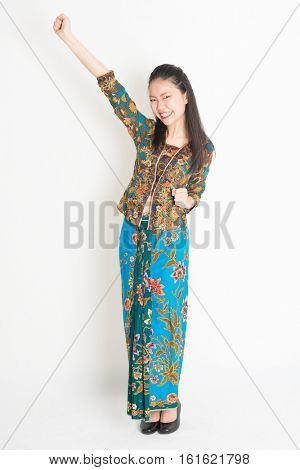 Portrait of young southeast Asian woman in traditional Malay batik kebaya dress arm raised celebrating success, full length standing on plain background.