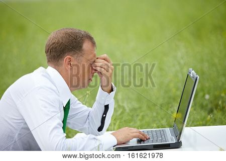 Manager working outdoors rubbing his eyes in nature