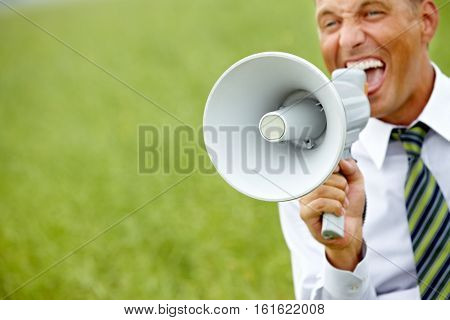 Manager shouting at big megaphone in nature