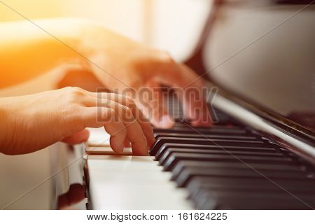 Scene of pianist hands from beside angle playing piano Photo in warm tone colors. Selective focus.