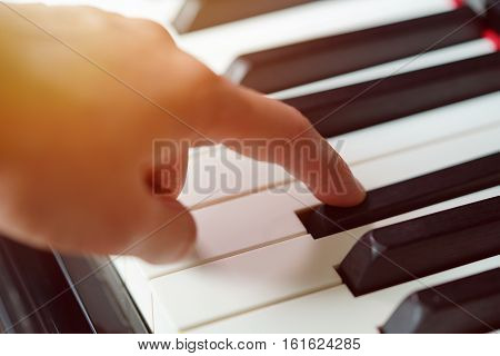 Scene of pianist finger press on the keypad piano Photo in warm tone colors. Selective focus.