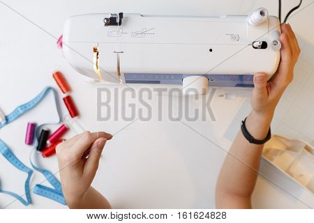 Girl preparing work on sewing-machine