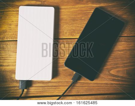 The power bank and smartphone on woodne table