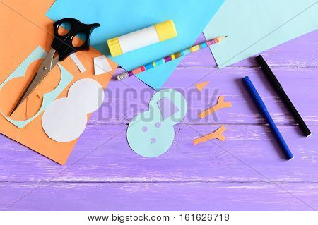 Making a children winter paper card. Step. Snowman parts cut from paper, scissors, markers, pencil, glue stick, colored paper set, snowman templates on wooden table. Kids winter DIY project. Top view
