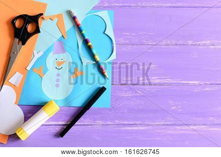 Paper card with snowman and words I love winter. Scissors, glue stick, pencil, markers, paper sheets and scraps on wooden background with copy space for text. Fun children winter background. Top view
