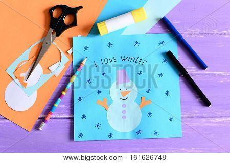 Making a children winter paper cards. Step. Paper card with snowman collage and text I love winter. Stationery and materials on wooden background. Kids winter crafts concept. Closeup. Top view