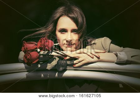 Sad young woman with red roses. Stylish fashion model outdoor