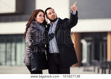 Happy young couple walking on city street. Stylish fashion model outdoor