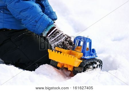 Children's games in the winter. Part of the image of a small child laying in the snow and plays with toy construction equipment.
