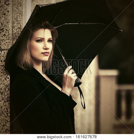 Happy woman with umbrella standing at the wall. Stylish fashion model outdoor