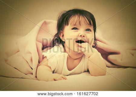Baby girl crawling on blanket indoors