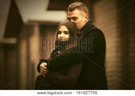 Happy young couple in love next to wooden cabin. Stylish fashion model outdoor
