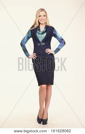 blond hair woman with straight hair style in blue blouse vest skirt high heel shoes going full body length isolated on white