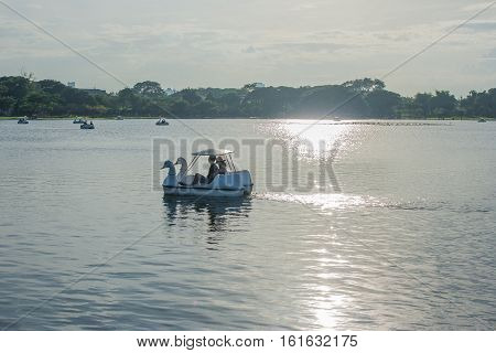 Pedal boat floating on the lake in public park, Thailand.