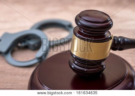 Gavel and handcuffs on a desk wooden
