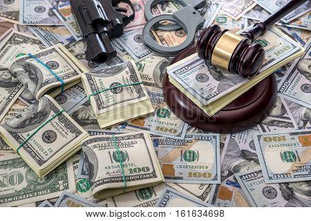 Judge gavel with money and handcuffs gun.