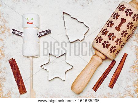Marshmallow snowman as a holiday food concept, top view. Christmas tree and star shaped cookie cutters, cinnamon sticks and wooden rolling pin on wood dusted with flour like a winter snow background.