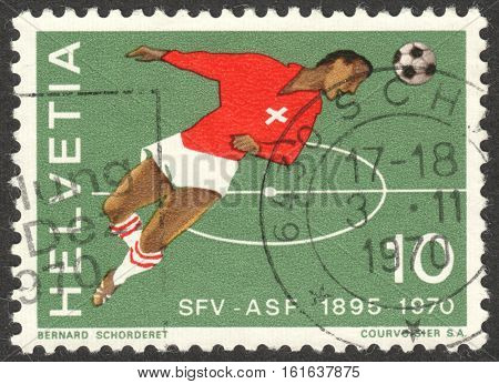 MOSCOW RUSSIA - CIRCA NOVEMBER 2016: a post stamp printed in SWITZERLAND shows a football player making a header circa 1970