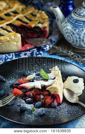 Seasonal summer berry tart with honeysuckle and rhubarb ice cream ball and teapot. Rustic style