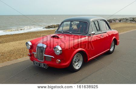 FELIXSTOWE, SUFFOLK, ENGLAND - AUGUST 27, 2016: Classic Red & Black Riley 1.5 motor car parked on seafront promenade.