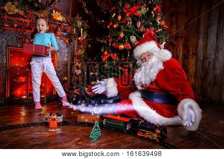 Good old Santa Claus playing with a child girl with toys under the Christmas tree. Christmas concept. Magic time.