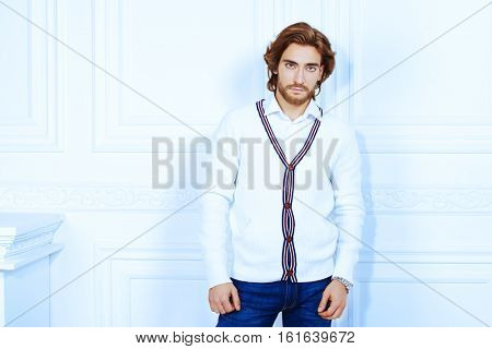 Attractive young man wearing white cardigan posing in luxurious interior. Men's beauty, fashion model. Hair styling.