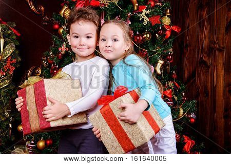 Christmas night. Little kids in pajamas sitting near a Christmas tree waiting for Christmas and gifts.