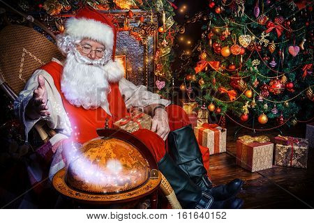 Christmas, tourist trip concept. Santa Claus at his home beautifully decorated for Christmas making plans of travelling around the planet. Christmas time. Time for miracles.