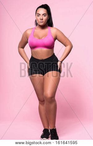 Just be yourself. Full length portrait of chubby mulatto woman standing against pink isolated background with arms on hips.