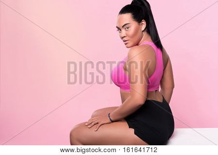 Be confident. Back view portrait of pretty chubby mulatto woman wearing sport clothing and looking forward while sitting against isolated pink background.