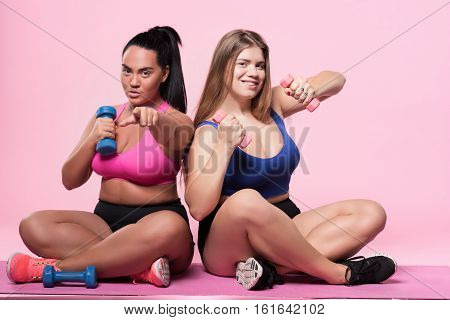 Go with us. Portrait of two pretty plump ladies sitting on floor against isolated pink background and doing exercises with small dumbbells.