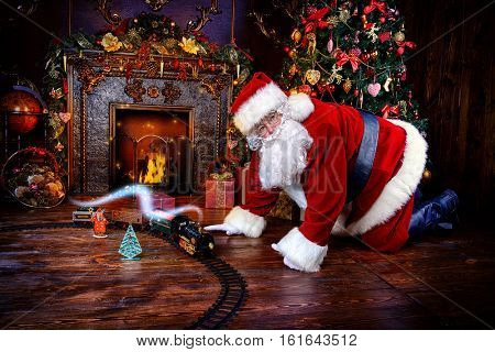 Happy Santa Claus playing with toys under the Christmas tree. Christmas concept. Magic time.