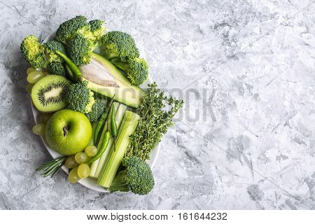 Farm green vegetables on gray marble background. Top view. Space for text. Greenery color