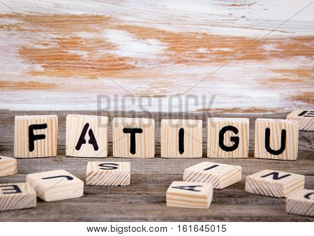 Fatigu from wooden letters on wooden background.