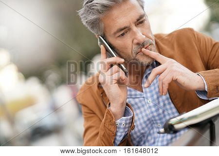 Businessman talking on phone with client, checking agenda