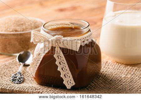 Caramel sauce on brown wooden background .