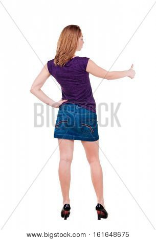 Back view of of young woman in jeans dress going thumb up. girl showing ok sign. isolated on white Rear view.Showing of positive emotions with OK sign concept .
