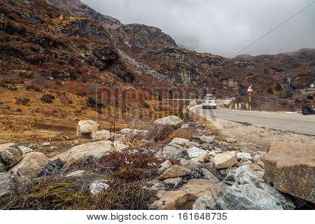 Rocky mountain road near Baba Mandir Sikkim on a foggy winter morning.