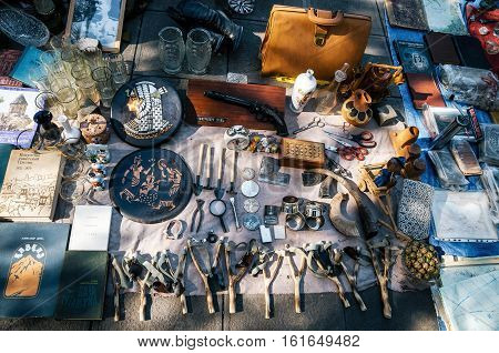 Tbilisi Georgia - October 15 2016: Flea market on Dry bridge having a lot of vintage plates handmade slingshot old gun faceted glass souvenirs and retro staff for the customers.