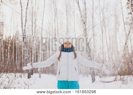 Beautiful girl in a white hat with earflaps throws snow up. Walk in the park in winter