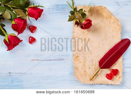 Red roses parchment quill pen and heart shaped chocolate candies on rustic wooden table.