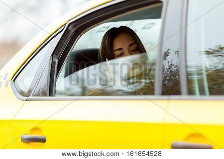 Beautiful girl sitting in yellow taxi for half-open window
